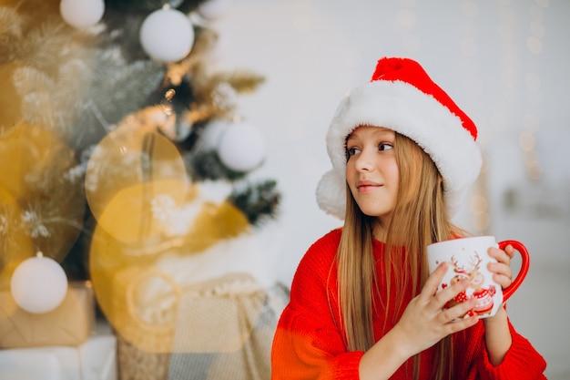 Mädchen, das kakao durch weihnachtsbaum trinkt