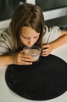 Mädchen, das kakao trinkt