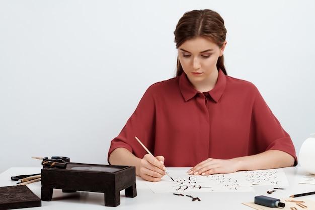 Mädchen, das kalligraphie auf postkarten schreibt. kunstdesign. über.