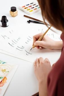 Mädchen, das kalligraphie auf postkarten schreibt. kunstdesign.