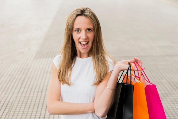 Mädchen, das kamera beim halten von einkaufstaschen betrachtet