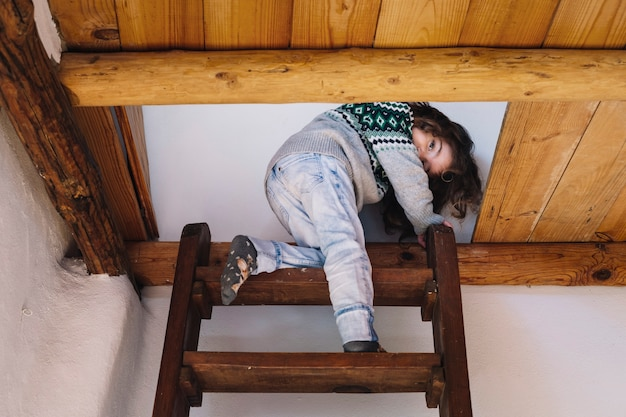 Mädchen, das kamera beim klettern der leiter betrachtet