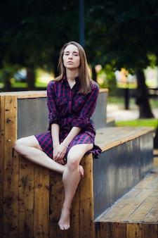 Mädchen, das kariertes kleid trägt, das im skatepark sitzt
