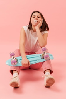 Mädchen, das kaugummi kaut und skateboard hält