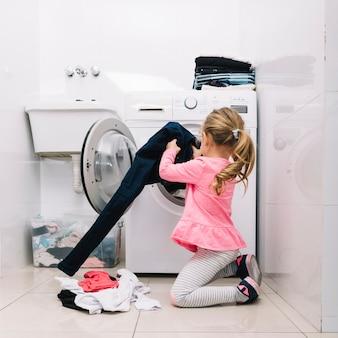 Mädchen, das kleidung in waschmaschine setzt
