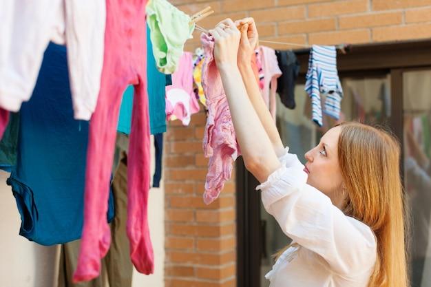 Mädchen, das kleidung nach wäscherei trocknet