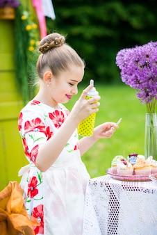 Mädchen, das kleine kuchen im hinterhof verziert