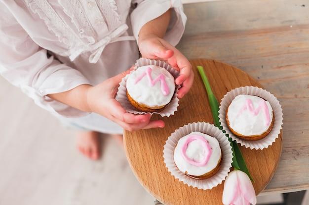 Mädchen, das kleinen kuchen mit mutteraufschrift hält