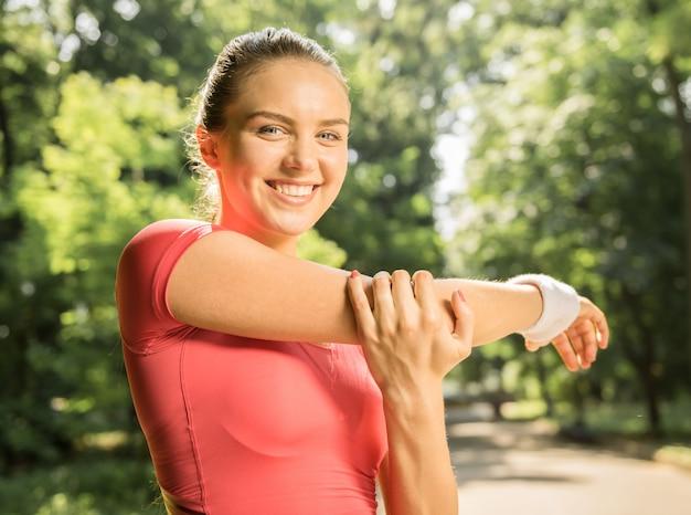 Mädchen, das körperliche übungen im park bei sonnenaufgang tut.