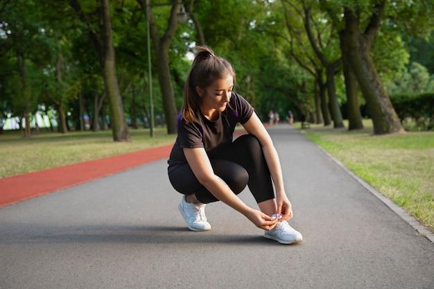 Mädchen, das körperliche übungen in einem stadtpark tut