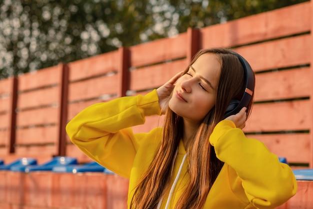 Mädchen, das kopfhörer auf der straße trägt