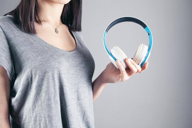 Mädchen, das kopfhörer in ihrer hand hält