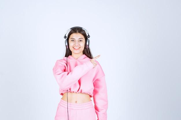 Mädchen, das kopfhörer trägt und rechte seite zeigt. hochwertiges foto