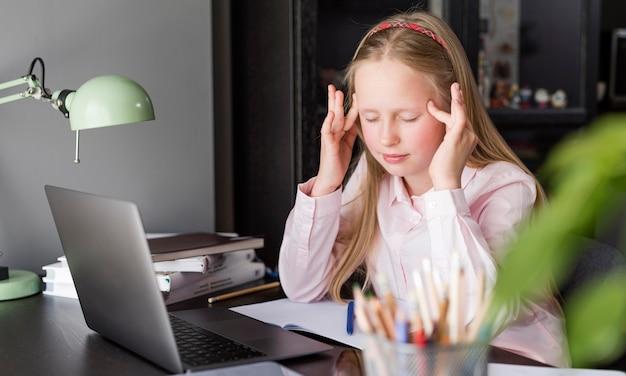 Mädchen, das kopfschmerzen nach einem online-kurs hat