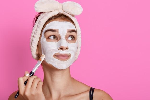 Mädchen, das kosmetische weiße gesichtsmaske empfängt, verträumt beiseite schaut, haarband mit schleife trägt, charmante dame, die anti-aging-verfahren zu hause am morgen tut.