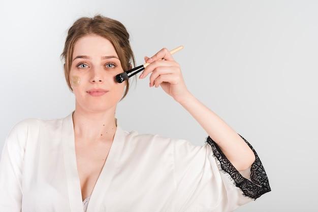Mädchen, das kosmetisches produkt sich aufträgt