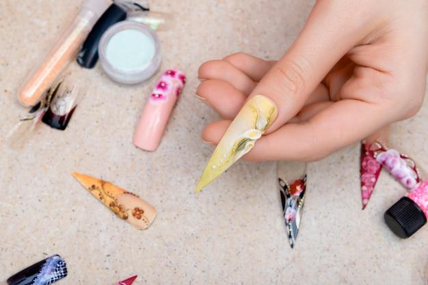 Mädchen, das künstliche nagelspitzen mit blumennageldesign versucht
