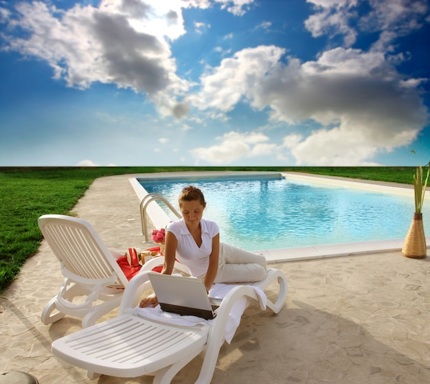 Mädchen, das laptop entlang einem swimmingpool verwendet