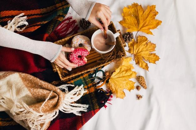 Mädchen, das leckeres frühstück im bett auf holztablett mit tasse kakao, zimt, keksen und glasierten donuts isst.
