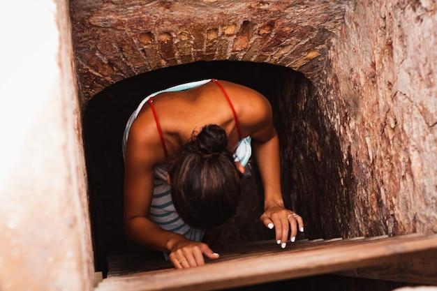 Mädchen, das leiter eines alten gebäudes klettert