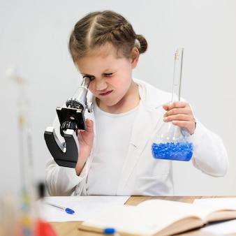 Mädchen, das lernt, wissenschaft mit mikroskop zu tun