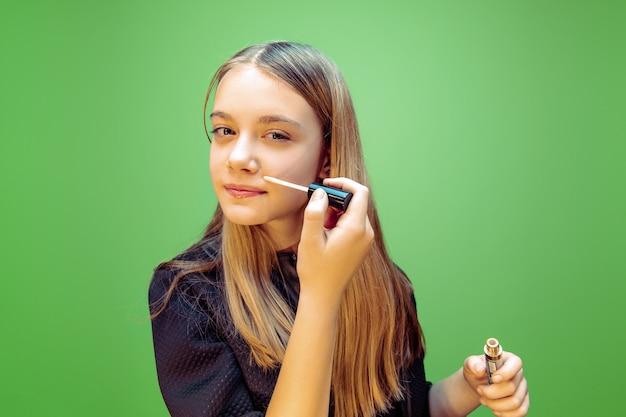 Mädchen, das lippenstift auf grün anwendet