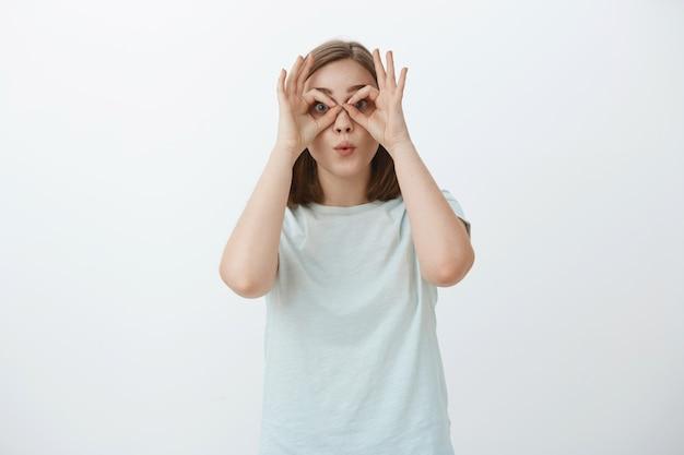 Mädchen, das lustige gesichter macht, die zeit verschwenden. porträt der verspielten und freudigen unreifen niedlichen frau im t-shirt, das kreise über augen mit händen macht, als ob durch schutzbrille schaut, die lippen herumfummelt