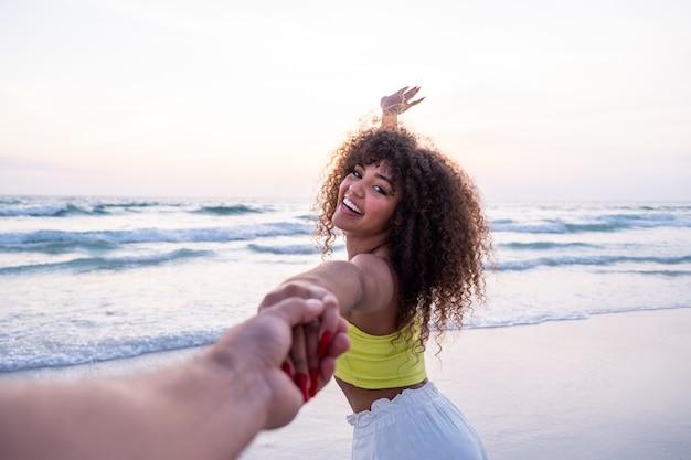 Mädchen, das männliche hand hält und auf tropischem exotischem strand zum ozean läuft