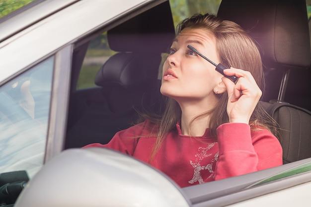 Mädchen, das make-up im auto tut. frau, dame beim fahren malt wimpern. frau schafft gefährliche situation auf der straße.