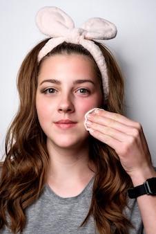 Mädchen, das make-up von ihrem gesicht mit wattepad auf grau entfernt