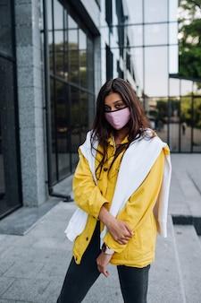 Mädchen, das maske trägt, die auf straße aufwirft. mode während der quarantäne des coronavirus-ausbruchs.