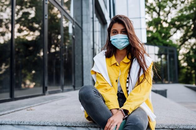 Mädchen, das maske trägt, die auf straße aufwirft.