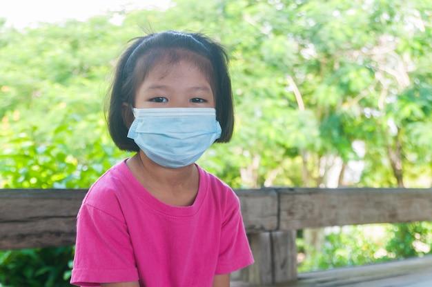 Mädchen, das medizinische maske trägt, während man im freien reist und auf bank sitzt