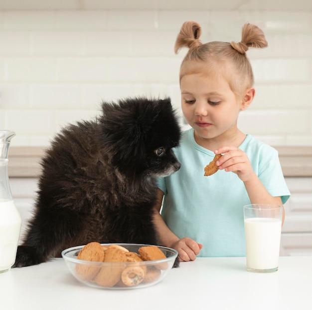 Mädchen, das milch trinkt und mit hund spielt