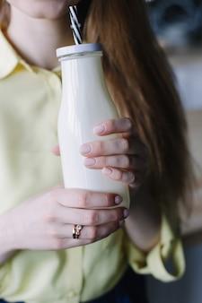 Mädchen, das milchshake in einer glasflasche trinkt