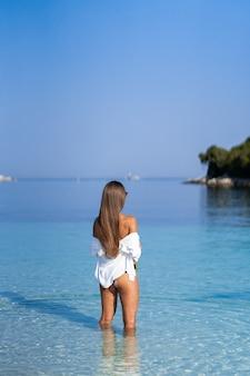 Mädchen, das mit alkohol aufwirft. sportliche glückliche frau, die in der trendigen sexy schwarzen badebekleidung joggt und die sonne genießt, die trainiert. gesunder lebensstil. spaß spazieren gehen. perfekte fitness-körperformen.