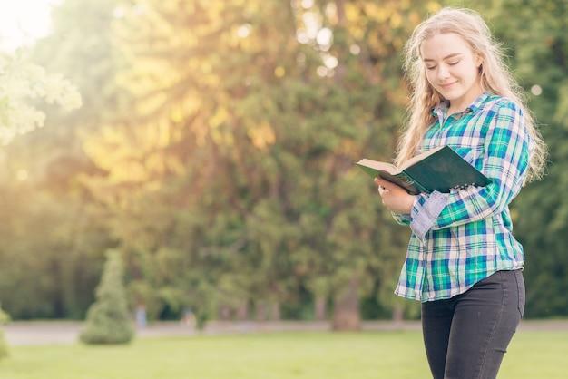 Mädchen, das mit buch im park studiert