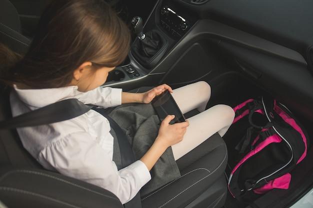 Mädchen, das mit dem auto zur schule fährt und handy benutzt