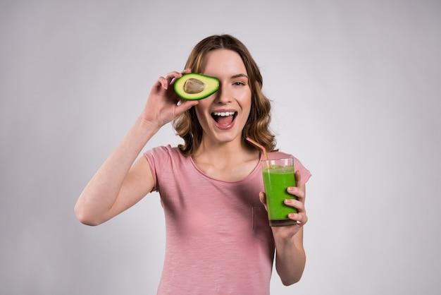 Mädchen, das mit dem grünen saft und avocado lokalisiert aufwirft.