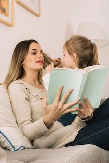 Mädchen, das mit dem haar der lesemutter spielt