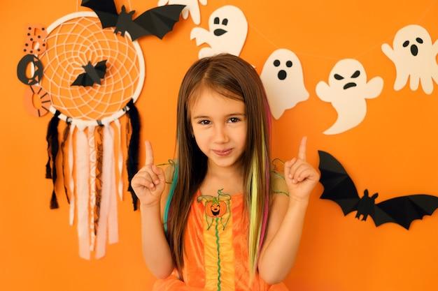 Mädchen, das mit den zeigefingern nach oben auf den kopierraum über dem studio-halloween-hintergrund zeigt