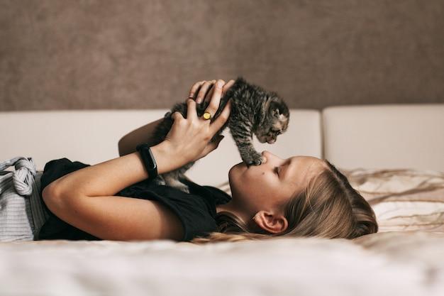 Mädchen, das mit einem britischen kleinen kätzchen spielt