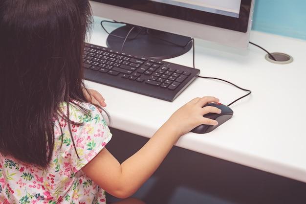 Mädchen, das mit einem computer spielt