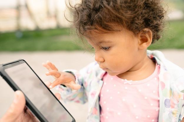 Mädchen, das mit einem handy berührt den schirm mit ihrem kleinen finger spielt