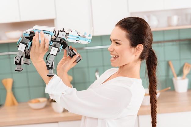 Mädchen, das mit einem nashornroboter in einer modernen schönen küche aufwirft.