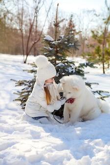 Mädchen, das mit einem shaggy weißen hund spielt. samojede im winter draußen im schnee.