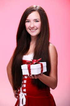 Mädchen, das mit einem weihnachtsgeschenk lächelt