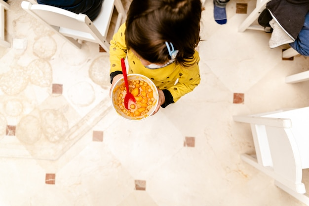Mädchen, das mit einer schüssel eintopfgericht im esszimmer ihres kindergartens geht