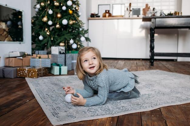 Mädchen, das mit einer weihnachtsverzierung spielt