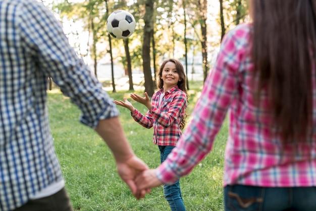 Mädchen, das mit fußball vor dem elternteil sich hält hand im park spielt